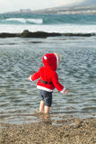 Kerstmanjongen bij het water van het zandstrand Stock Fotografie