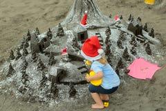 Kerstmanjongen met zandig kasteel Royalty-vrije Stock Fotografie