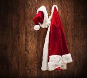 Kerstmankostuum het hangen op een houten muur Stock Fotografie
