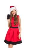 Kerstmanmeisje die een mobiele telefoon voorstellen Stock Foto