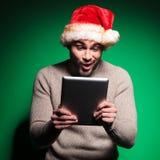 Kerstmanmens die wordt verbaasd over wat hij op tablet leest Stock Foto