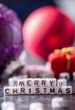 Kerstmis De tijd van Kerstmis De decoratie van Kerstmis Woorden Vrolijke Kerstmis met rode Kerstmisdecoratie Stock Afbeeldingen