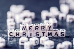 Kerstmis De tijd van Kerstmis De decoratie van Kerstmis Woorden Vrolijke Kerstmis met rode Kerstmisdecoratie Stock Afbeelding
