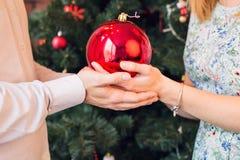 Kerstmis, decoratie, vakantie en mensenconcept - sluit omhoog van vrouw en man Kerstmis rode bal van de handholding Royalty-vrije Stock Foto