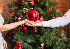 Kerstmis, decoratie, vakantie en mensenconcept - sluit omhoog van vrouw en man Kerstmis rode bal van de handholding Royalty-vrije Stock Afbeeldingen