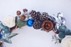 Kerstmis decoratieve kroon van kegel, kunstbloemen, klimopbladeren en sparrenballen Stock Foto's