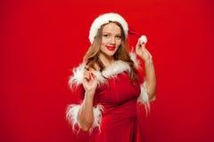 Kerstmis Dicht omhooggaand portret van mooi sexy meisje die de kleren van de Kerstman, over rode achtergrond dragen stock foto's