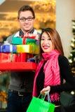 Kerstmis die van het paar winkelt met stelt in wandelgalerij voor Stock Afbeelding