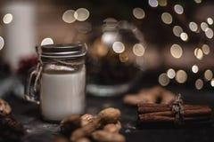 Kerstmis en de nieuwe achtergrond van de jaardecoratie met ronde bokeh slinger, kaneel, koekjes, kegels, noten en kaars in kop royalty-vrije stock afbeeldingen