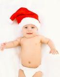 Kerstmis en familieconcept - leuke glimlachende baby in rode santahoed die op wit bedhuis liggen Royalty-vrije Stock Afbeeldingen