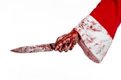 Kerstmis en Halloween als thema hebben: De bloedige handen van de kerstman van een gek die een bloedig mes op een geïsoleerde wit stock fotografie