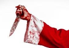 Kerstmis en Halloween als thema hebben: De bloedige handen van de kerstman van een gek die een bloedig mes op een geïsoleerde wit royalty-vrije stock foto's