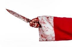 Kerstmis en Halloween als thema hebben: De bloedige handen van de kerstman van een gek die een bloedig mes op een geïsoleerde wit stock afbeelding