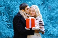 Kerstmis en mensenconcept - gelukkige mens die een doosgift geven stock afbeelding