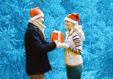 Kerstmis en mensenconcept - gelukkige mens die een doosgift geven stock foto's