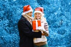 Kerstmis en mensenconcept - gelukkige mens die een doosgift geven royalty-vrije stock afbeeldingen