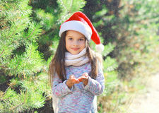 Kerstmis en mensenconcept - meisjekind in blazende sneeuw van de santa de rode hoed in handen stock afbeeldingen
