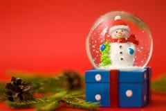 Kerstmis en nieuwe jaarkaart met binnen de sneeuwman van de sneeuwbol De doos van de gift op rode achtergrond Vakantie, de winter royalty-vrije stock afbeelding