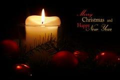 Kerstmis en nieuwe jaarkaart met kaars en rode snuisterijen, steekproef Royalty-vrije Stock Fotografie