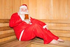 Kerstmis en Nieuwjaar Grappige kerel in een Kerstmankostuum Grappige Kerstman in de Finse sauna Stock Foto
