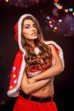 Kerstmis en Nieuwjaar Vrouw in santakostuum met kap die zich bij het zwarte gekruiste wapens sassy glimlachen bevinden royalty-vrije stock foto's