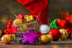 Kerstmis en Nieuwjaarachtergrond met Miniatuurboodschappenwagentje Stock Foto's