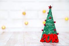 Kerstmis en Nieuwjaarachtergrond met rode houten cijfers 2018 dichtbij het licht van de Kerstmisboom witn en ster aangaande de ac Royalty-vrije Stock Afbeelding