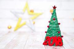 Kerstmis en Nieuwjaarachtergrond met rode houten cijfers 2018 dichtbij het licht van de Kerstmisboom witn en ster aangaande de ac Stock Fotografie