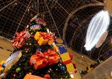 Kerstmis en Nieuwjaarboom en decoratie van de Belangrijkste Universele Opslaggom op Rood Vierkant stock foto