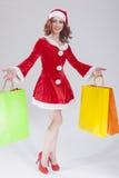 Kerstmis en Nieuwjaarconcept en Ideeën Het sexy Kijken Jong Kaukasisch Rood Haired Wijfje in Santa Hat Posing With Shopping-Zakke Stock Foto
