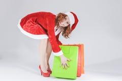 Kerstmis en Nieuwjaarconcept en Ideeën Het sexy Kijken Jong Kaukasisch Rood Haired Wijfje in Santa Hat Posing With Shopping-Zakke Stock Afbeeldingen