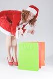 Kerstmis en Nieuwjaarconcept en Ideeën Het sexy Kijken Jong Kaukasisch Rood Haired Wijfje in Santa Hat Posing With Shopping-Zakke Royalty-vrije Stock Foto's