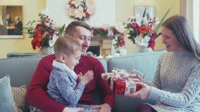 Kerstmis Family De vrouw stelt een Kerstmisgift aan haar echtgenoot voor stock videobeelden