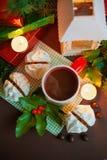 Kerstmis feestelijke samenstelling - een mok met Santa Klais, cakes, kaarsen, takken van hulst, bessen en dozengiften  Stock Afbeeldingen