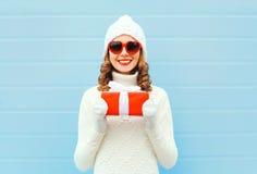 Kerstmis gelukkige glimlachende jonge vrouw met giftdoos die de gebreide zonnebril van de hoedensweater over blauwe achtergrond d Royalty-vrije Stock Afbeeldingen