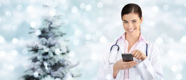 Kerstmis glimlachende arts met slimme telefoon op vage lichten royalty-vrije stock foto