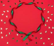 Kerstmis golvend lint om kader op rode achtergrond royalty-vrije stock afbeeldingen