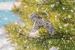 Kerstmis houten stuk speelgoed paard op de boom van de de winterpijnboom royalty-vrije stock fotografie