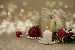 Kerstmis Huidig met kaars en rode snuisterijen. Stock Afbeelding