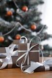 Kerstmis huidig op verfraaide boomachtergrond, vakantieconcept Stock Foto