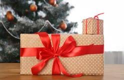 Kerstmis huidig op verfraaide boomachtergrond, vakantieconcept Stock Fotografie