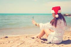 Kerstmis jonge glimlachende vrouw in rode santahoed die beeld zelfportret op smartphone nemen bij strand over overzeese achtergro stock afbeelding