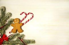 Kerstmis, Kerstmispeperkoek en karamelriet met kunstmatige Kerstboomtakken stock afbeelding