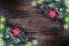 Kerstmis Kerstmisspar met ster en denneappel op rustieke houten lijst Diagonaal samenstellingsgrens in sneeuwatmosfeer Royalty-vrije Stock Afbeeldingen