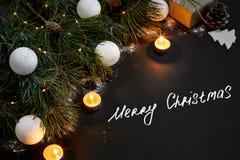 Kerstmis Kerstmisspeelgoed, brandende kaarsen en nette tak op zwarte hoogste mening als achtergrond Ruimte voor tekst Royalty-vrije Stock Afbeeldingen