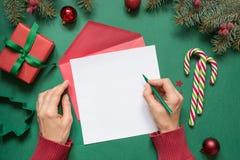 Kerstmis lege spatie voor brief aan Kerstman of uw wishlist of komstactiviteiten op groen Vrouwelijke hand die op pagina schrijft stock afbeeldingen