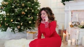 Kerstmis, meisje in feestelijke kledij, die op een celtelefoon spreken, die in de woonkamer dichtbij de Kerstboom, Nieuwjaar zitt stock videobeelden