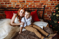 Kerstmis Moeder en zoonszitting op een bed in een ruimte met een bakstenen muur Stock Foto