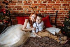 Kerstmis Moeder en zoonszitting op een bed in een ruimte met een bakstenen muur Stock Fotografie