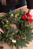Kerstmis natuurlijke kroon De bloemists handen die natuurlijke Kerstmiskroon, Kerstmisdecoratie met natuurlijke spar maken vertak stock afbeelding